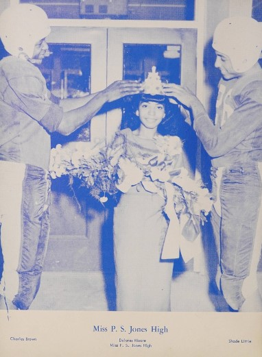 A photo from the yearbook depicting the crowning of Miss P.S. Jones by two football players.