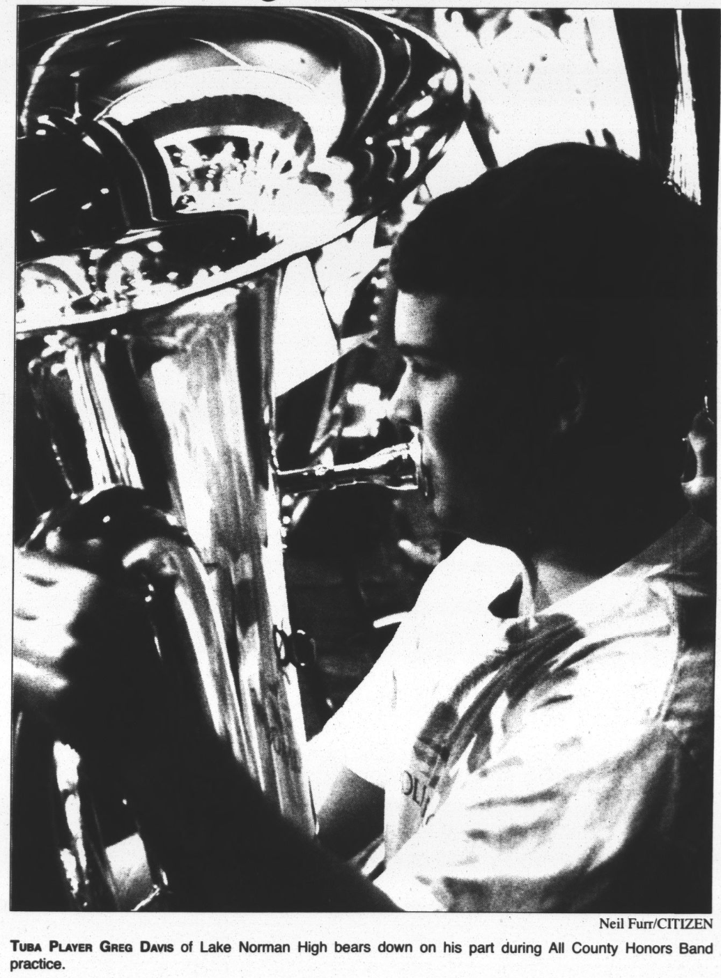 """Photograph of a high school student playing the tuba. The caption under the photo reads, """"Tuba Player Greg Davis of Lake Norman High bears down on his part during All County Honors Band practice. Photo taken by Neil Furr."""