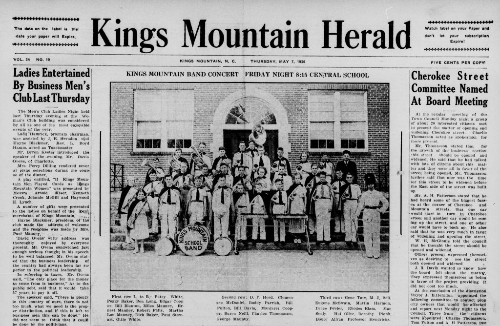 Black and white image of front page of English language newspaper, with photo of school children in uniforms standing on outdoor steps