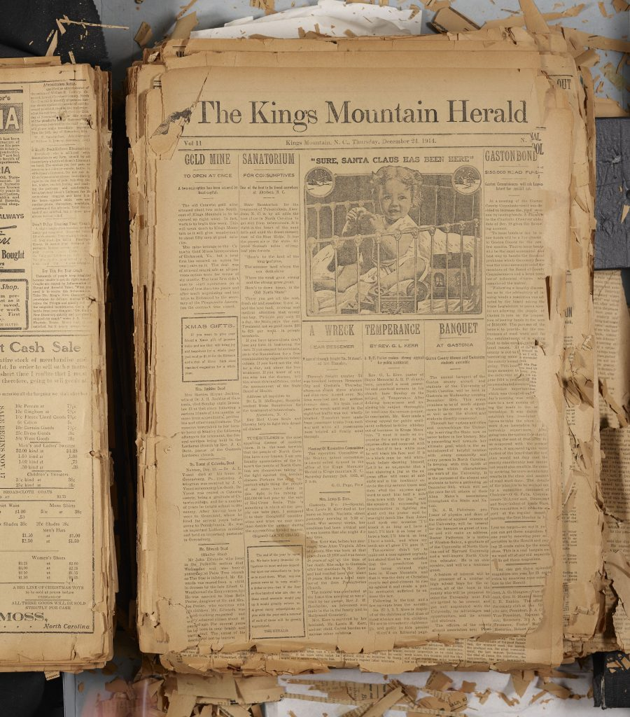 Stack of yellowed English language newspapers with pieces of broken off paper on the table around the edges