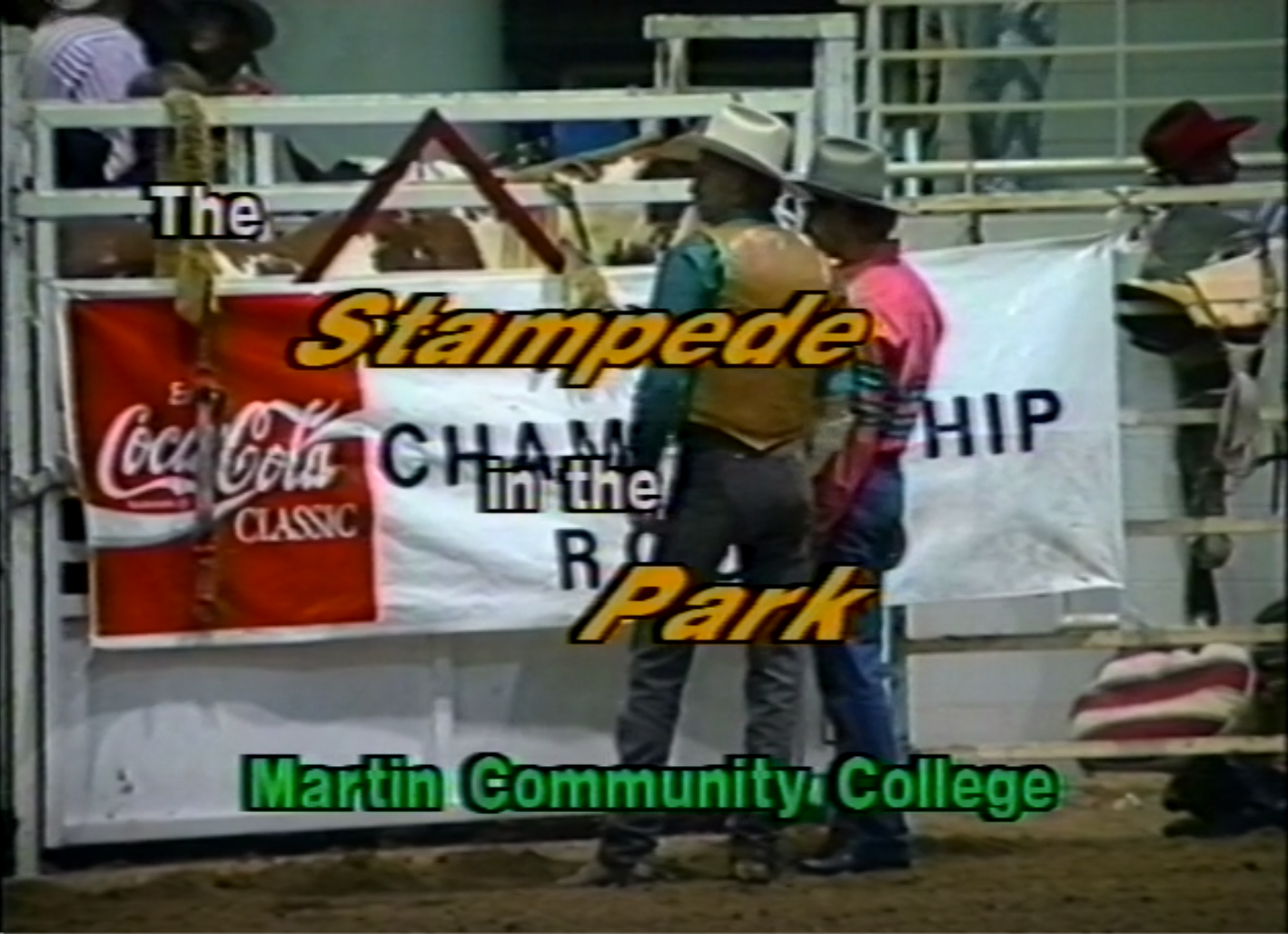 """Title card for The Stampede in the Park, Rodeo, 1992 video. Two people standing participating in a rodeo standing in front of an advertisement. Over the picture the worlds """"The Stampede in the Park, Martin Community College."""""""