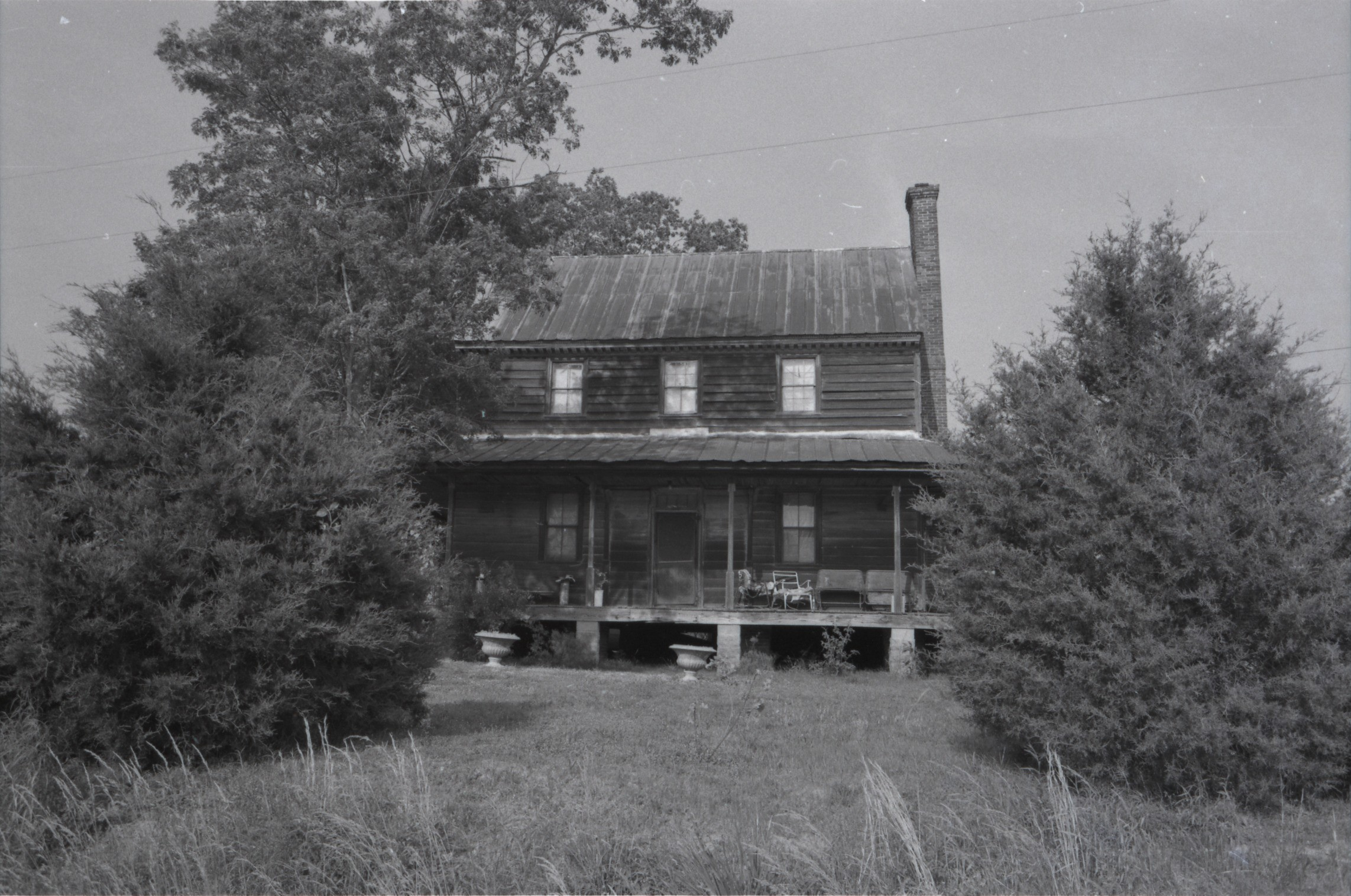 Black and white photograph of an older looking two story house.