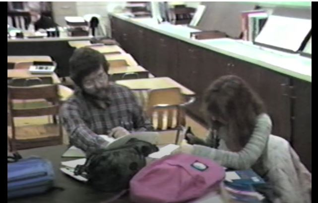Two students sit at a table looking at notebooks with bookbags on the table.